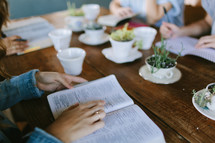 young women sitting around a table reading Bibles