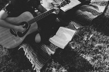young woman sitting on a blanket playing a guitar and reading a Bible