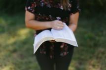 torso of a teen girl reading a Bible