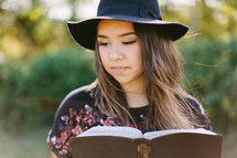 teen girl in a hat reading a Bible