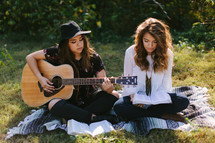 teen girls sitting on a blanket outdoors playing a guitar and singing