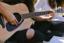 teen girls sitting on a blanket outdoors playing a guitar