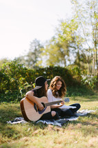 young women sitting on a blanket outdoors playing a guitar and singing