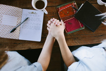 young women holding hands in prayer at a Bible study