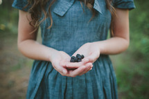 girl with hand full of blackberries