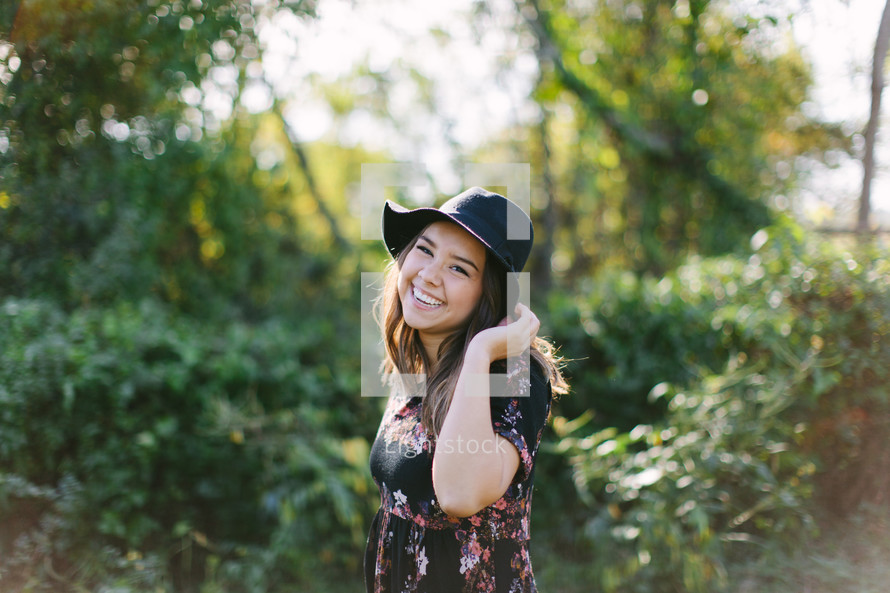 portrait of a teen girl in a hat standing outdoors