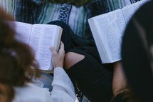 young woman sitting on a blanket outdoors reading Bibles