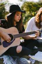 teen girl playing a guitar on a blanket