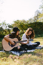 young women sitting on a blanket outdoors reading Bibles and playing a guitar