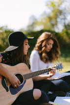 young women sitting on a blanket outdoors reading Bibles and playing guitars