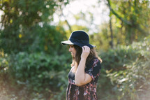 young woman in a hat standing outdoors