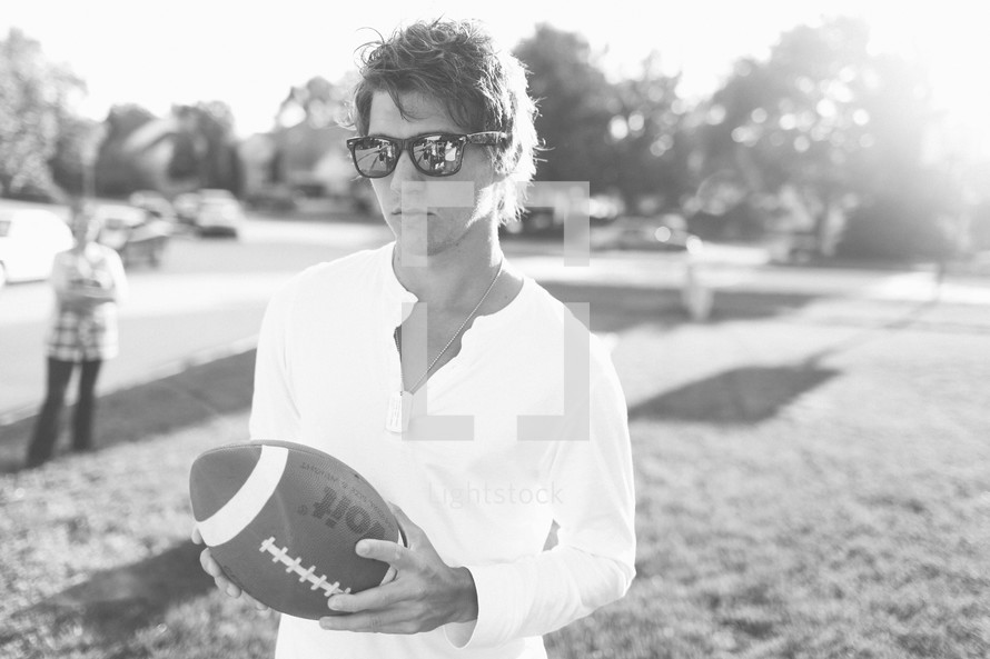 Man with sunglasses holding football in park