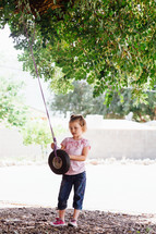 a girl child playing with a tire swing