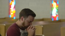 a man praying alone in a church