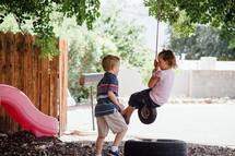 children swinging on a tire swing outdoors