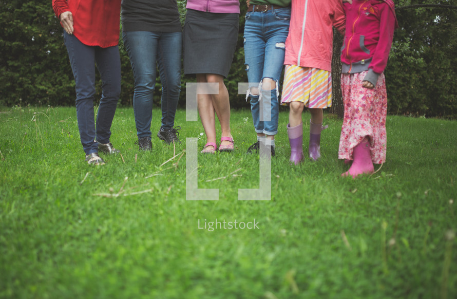 legs of girls standing in grass
