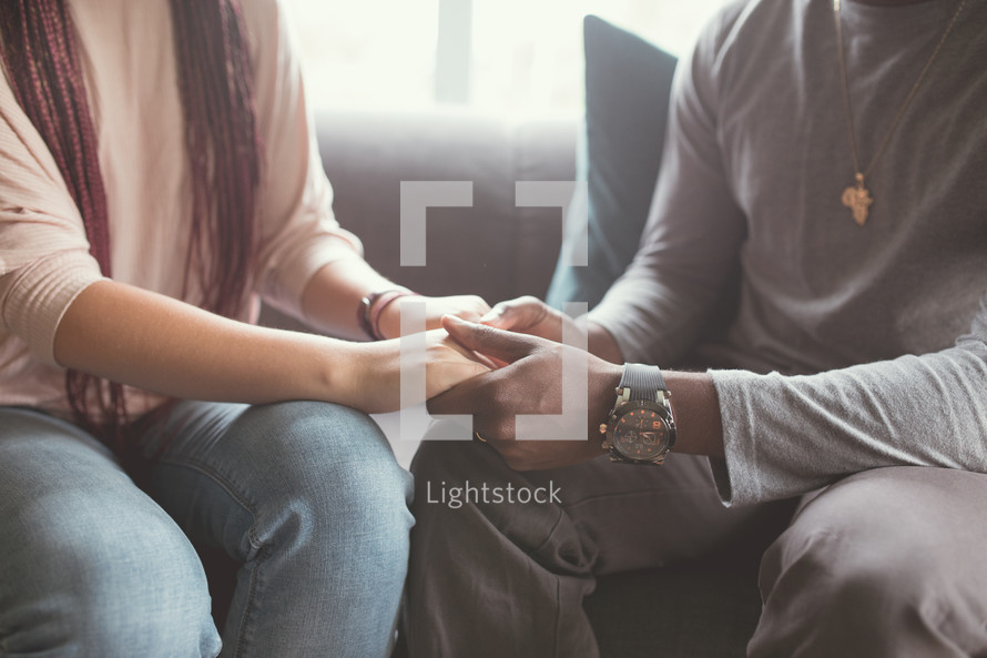 a couple holding hands sitting on a couch