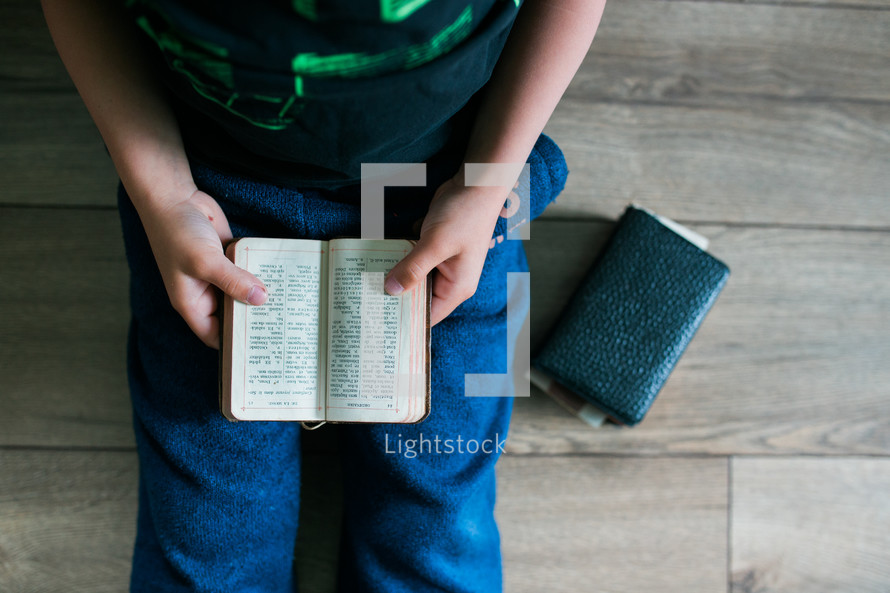 a boy reading a Bible
