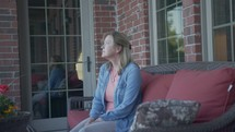 a woman sitting quietly on a porch
