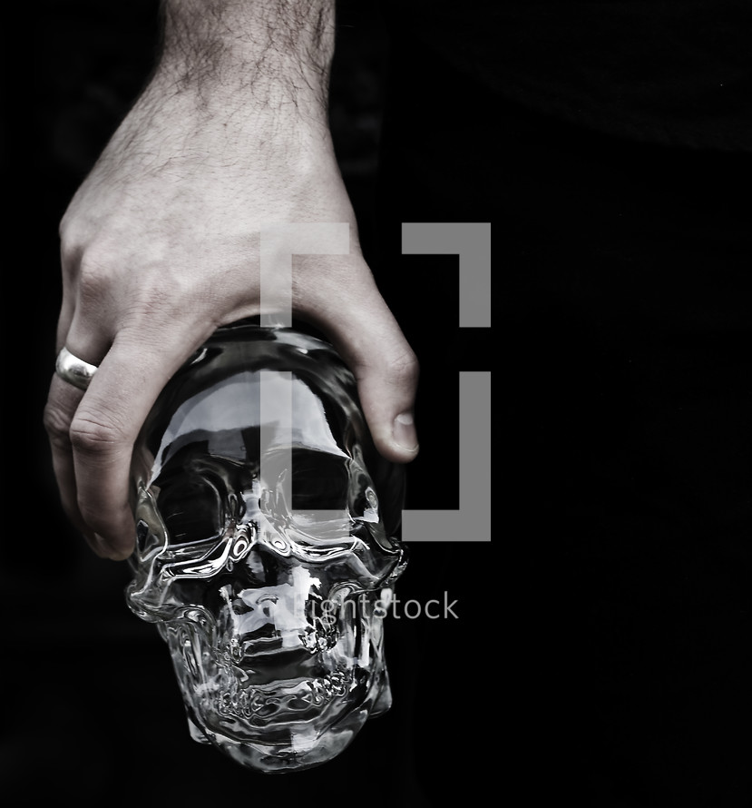 Man holding glass skull with ring on middle finger.