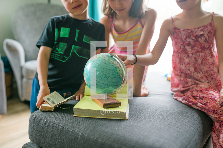 children studying a globe