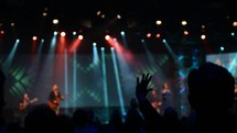 Silhouette of an audience with arms raised at a concert with colorful stage lighting.
