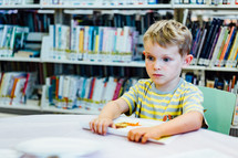 a boy reading in a library