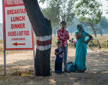 children in front of a restaurant sign in India