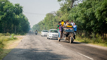 people loaded onto a crowded vehicle traveling on a road in India