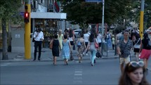time-lapse of people crossing a street at a crosswalk in a city