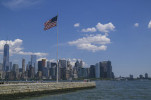 American flag on a flag pole and view of a city