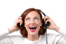 A woman listening to headphones with an excited look on her face.