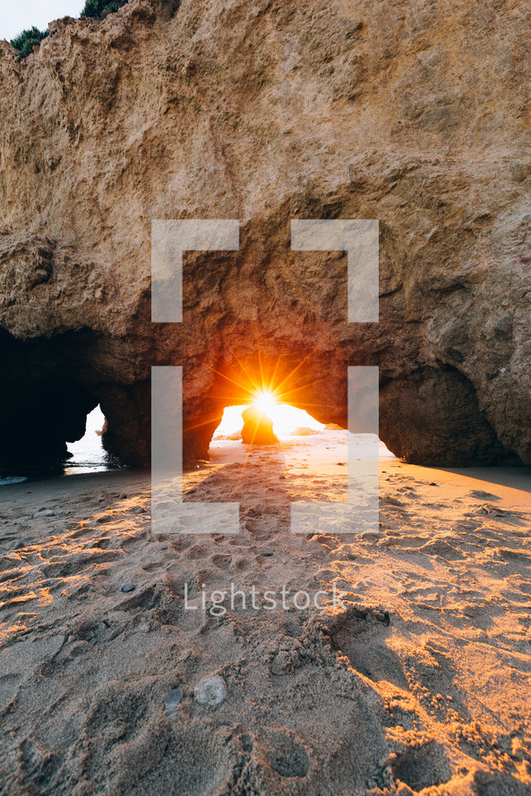 Sunrise seen through a rock arch on a sandy beach.