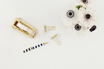 pen, tape dispense, gold, clubs, desk, white, flowers, black centers, white background