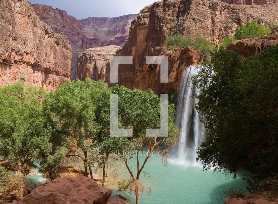 waterfall off a red rock cliff