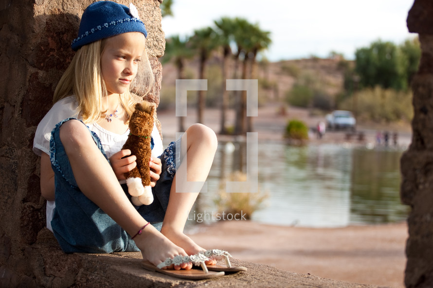 girl child sitting holding a stuffed animal horse
