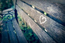 A small heart painted on a wooden park bench with shallow focus.