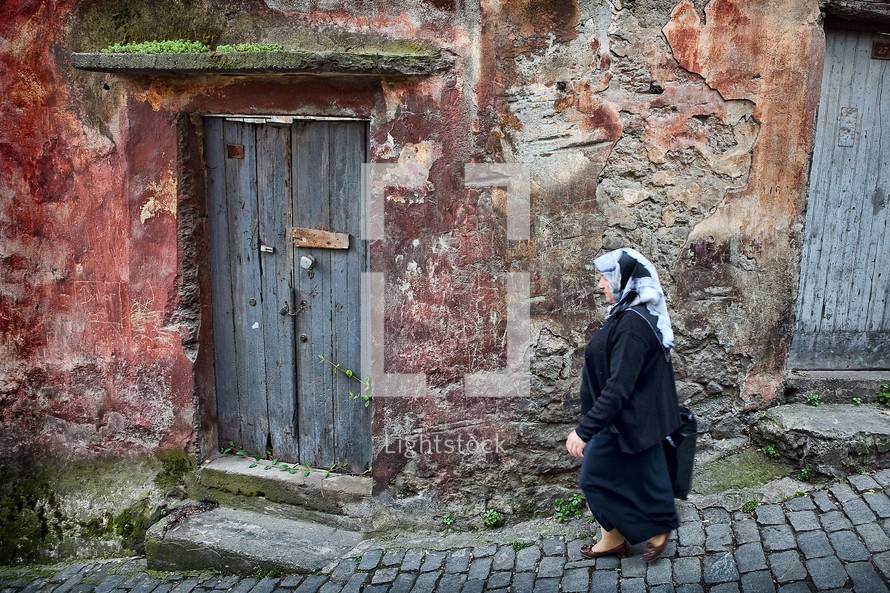Muslim woman walking cobblestone