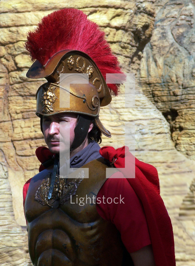 A Roman Soldier dressed in full military gear including helmet, breastplate and cape stands guarding the Tomb of Christ.