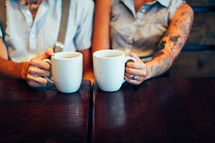 couple holding coffee mugs