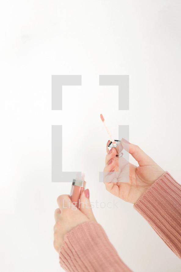 a woman putting on lipstick