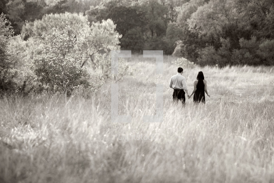 couple holding hands walking in a field