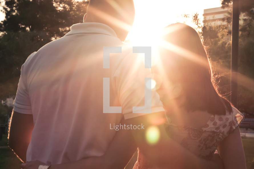 Couple with arms around each other's backs with sun beam shining between them.