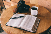 An open Bible, cup of coffee, and camera on a table.