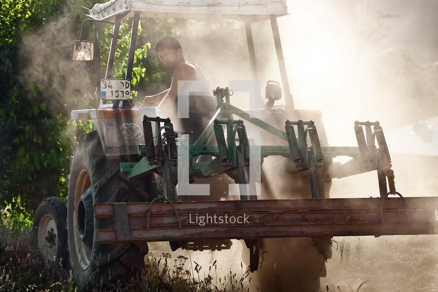 Male farmer driving tractor
