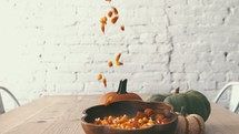 candy corn falling into a bowl