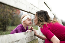 a mother kissing her toddler daughter through fence slats