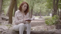 a woman walking in a park carrying a Bible and sitting down to read