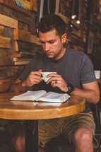 A man sits at a table in a cafe reading the Bible and drinking coffee.