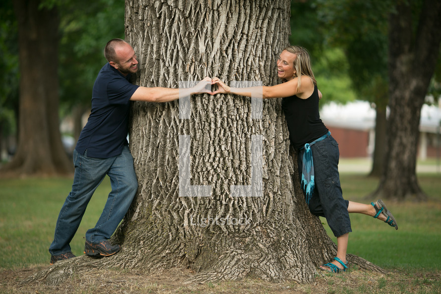 couple making a heart with their hands around a tree trunk